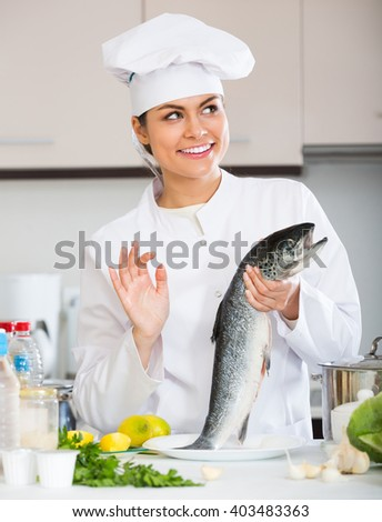 Happy smiling female cook preparing big fish in restaurant