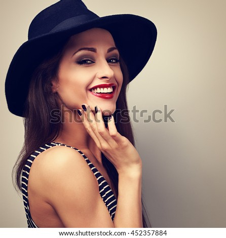 Happy smiling female model in black elegant hat. Vintage toned closeup portrait - stock photo