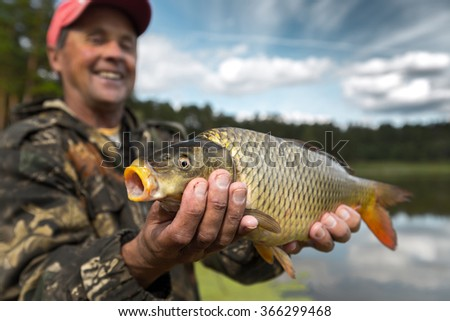 Happy smiling fisherman holding his trophy carp (Cyprinus carpio) with lake on the background. Focus on the fish - stock photo