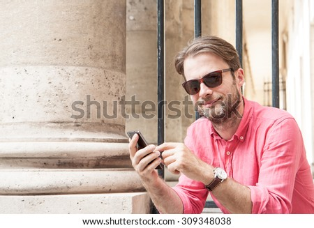 Happy smiling forty years old caucasian man in sunglasses touching mobile phone screen (smartphone) outdoor in the city. - stock photo