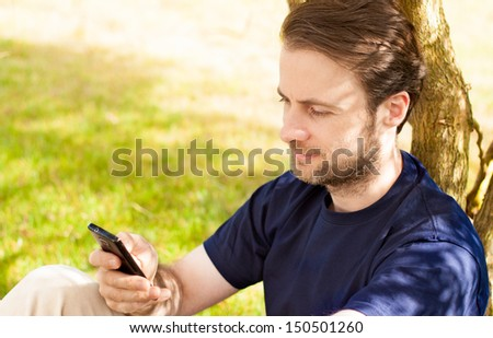 Happy smiling forty years old caucasian man looking on a mobile phone outdoor in a park while sitting by a tree during a sunny summer day - stock photo