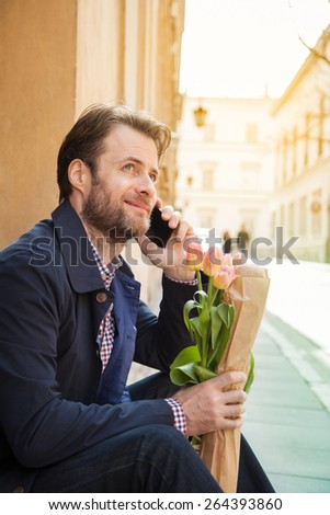 Happy smiling forty years old caucasian man with baguette and flower bouquet talking on a mobile phone. Street and city buildings as background. - stock photo