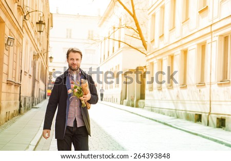 Happy smiling forty years old caucasian man with baguette and flower bouquet walking down the street. City buildings as background. - stock photo
