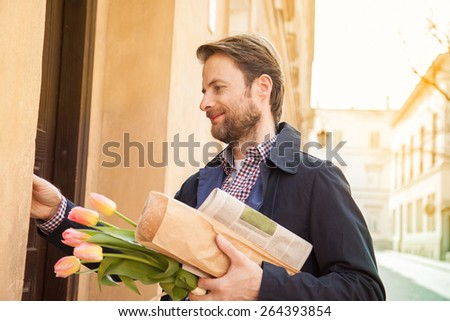 Happy smiling forty years old caucasian man with baguette, newspaper and flower bouquet ringing doorbell. Street and city buildings as background.  - stock photo