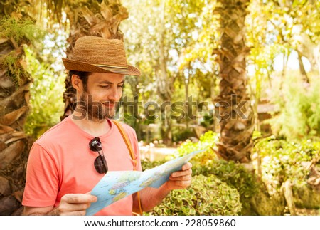 Happy smiling forty years old caucasian tourist man looking at the map outdoor among exotic palm trees - summer holiday traveling - stock photo