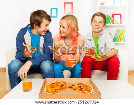 Happy smiling friends eat together pizza at home - stock photo