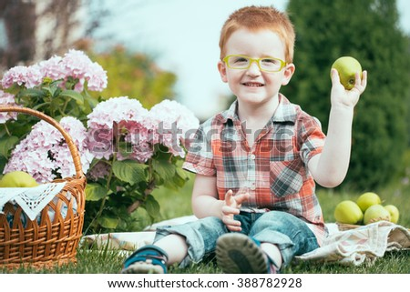 Happy smiling funny small red haired boy in stylish checkered shirt jeans and yellow glasses sitting outdoor on picnic with basket of green apples near flowers on natural backdrop, horizontal picture - stock photo