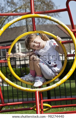 happy, smiling girl climbing on the playground - stock photo