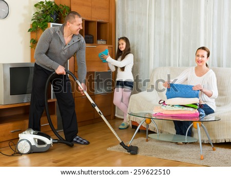 Happy smiling girl helping happy parents to clean at living room. Focus on man - stock photo