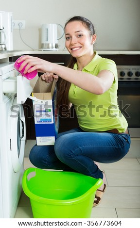 Happy smiling girl holding box with detergent during laundry 