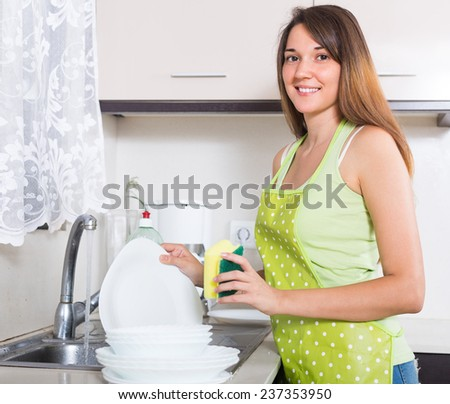 Happy smiling girl in apron washing plates with sponge in domestic kitchen
