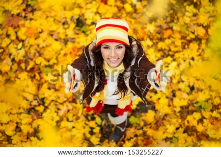 Happy smiling girl in autumn park, top view