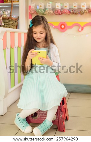 Happy smiling girl  in  beautiful blue dress sitting on a chair at the candy store and playing tablet - stock photo