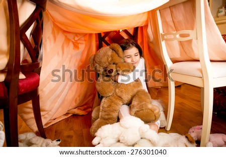 Happy smiling girl in pajamas hugging teddy bear at self-made house - stock photo