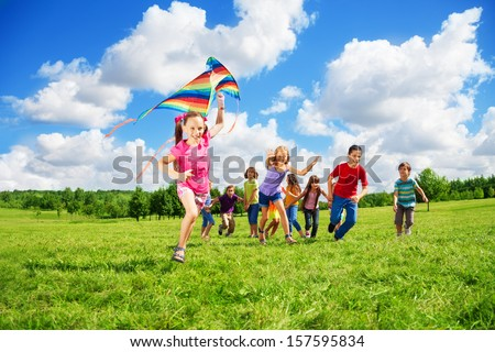 Happy smiling girl in pink with long hair with other kids boys and girls running after her