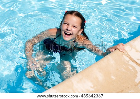 Happy smiling girl in the pool