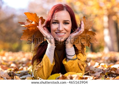 Happy smiling girl lying in autumn leaves
