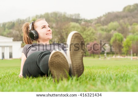 Happy smiling girl lying on back and listening music on green grass in the park - stock photo