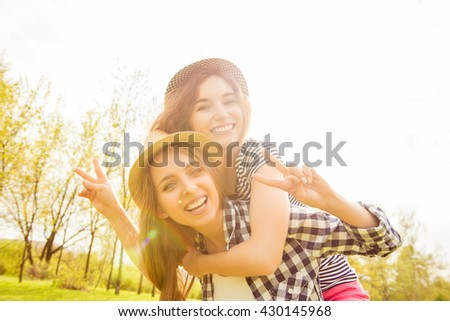 Happy smiling girl piggybacking her sisters and gesturing with two fingers - stock photo