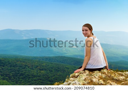 Happy smiling girl sitting on a cliff side - stock photo