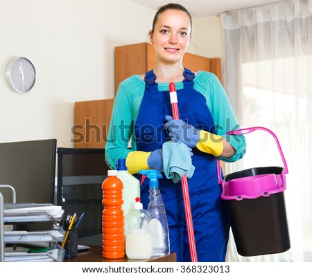Happy smiling girl standing with cleaning equipment