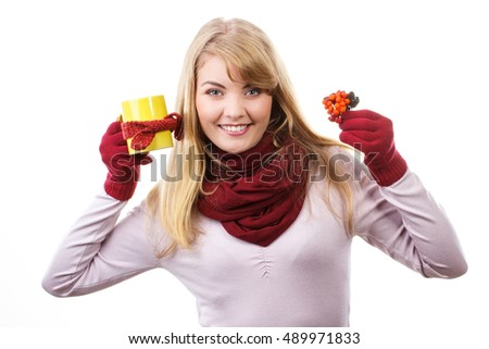 Happy smiling girl wearing woolen shawl and gloves, holding autumnal decoration and cup of hot tea wrapped scarf, warming drink, white background