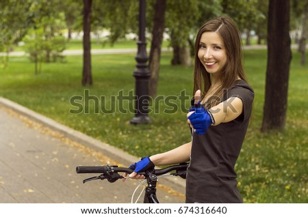 Happy smiling girl with bicycle showing thumbs up sign. Healthy lifestyle concept.