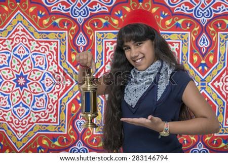 Happy Smiling Girl with Lantern Celebrating Ramadan over Ramadan Fabric - stock photo
