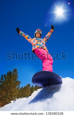 Happy smiling girl with lifted hands stand on snowboard about to slide downhill the mountain - stock photo