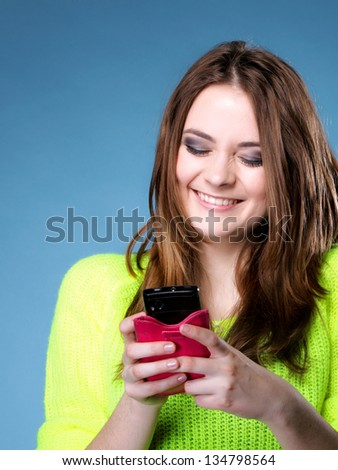 Happy smiling girl with mobile phone reads message , blue background - stock photo
