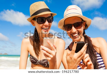 Happy smiling girls using mobile smart phone on the beach.  - stock photo