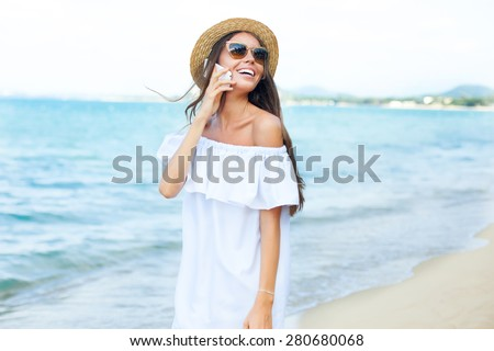 Happy smiling girls using mobile smart phone on the beach.woman funky happy and colorful wearing sunglasses and beach hat having summer fun during travel holidays vacation.traveling,summertime - stock photo