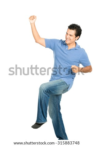 Happy smiling good looking hispanic male in casual clothes, no shoes celebrating indoors with victorious fist pump into the air looking away from camera