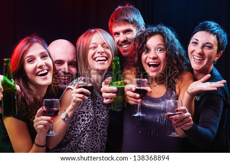 Happy smiling group of friends enjoying at the disco club with drinks in their hands. - stock photo