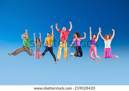 Happy smiling  group of jumping  over the blue sky. Serbia. - stock photo