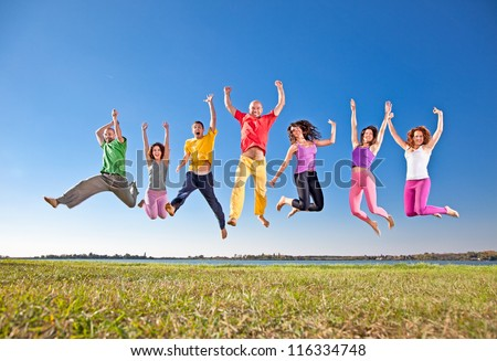Happy smiling  group of jumping  people on banch of lake - stock photo