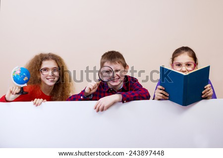 Happy smiling group of kids, friends, boys and girls, learning showing white blank placard, board,poster. - stock photo
