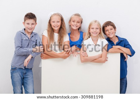 Happy smiling group of teens, friends, boys and girls, showing blank placard board to write it on your own text  on white background - stock photo