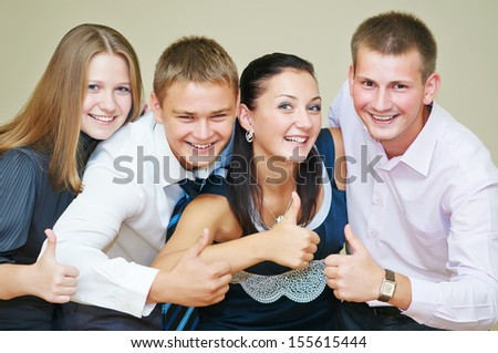 Happy smiling group of young friends with thumbs up - stock photo