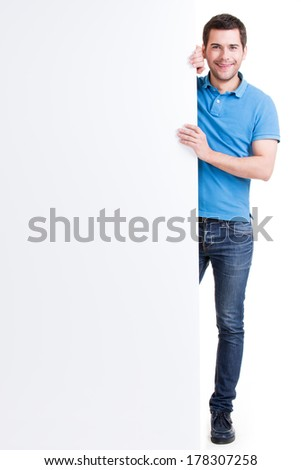 Happy smiling handsome young man look out from blank banner - isolated on white.