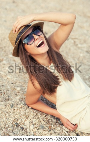 Happy smiling hipster woman in hat on a sea beach. - stock photo
