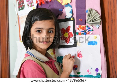 Happy/smiling Indian school girl/kid/student learning/drawing/decorating pin board in her art class room, wearing pink and beige uniform Kerala, India. green desk/table. Education of Asian girl child.