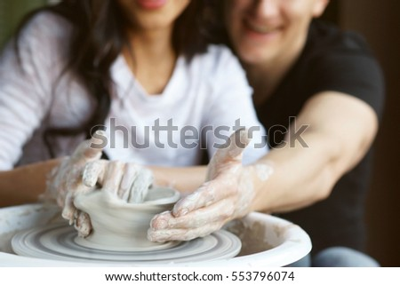 Happy smiling joyful romantic couple working together on potter wheel and sculpting clay pot. Focus on dirty hands.
