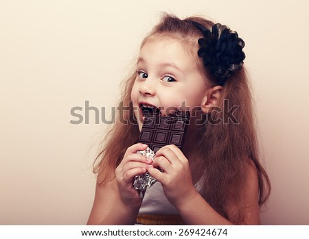 Happy smiling kid girl biting tasty chocolate with empty copy space. Vintage portrait - stock photo