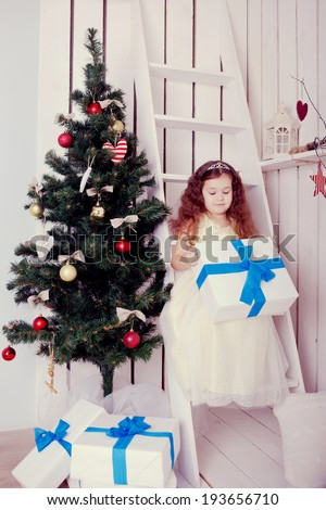 Happy smiling kid holding gifts near the Christmas tree. Christmas, New Year, holiday concept, ready for your text. Retro style.  - stock photo