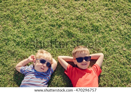 Happy smiling kids relaxing on green grass under sun, top view with copy space. Color-toning applied