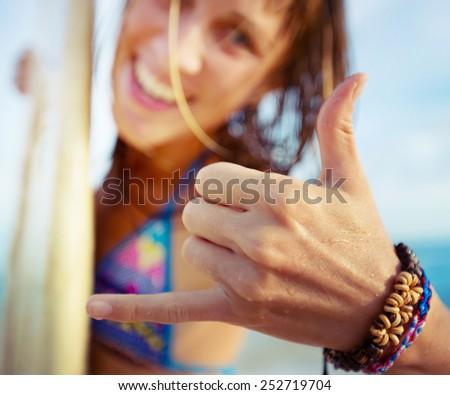 Happy smiling lady surfer showing shaka sigh. - stock photo