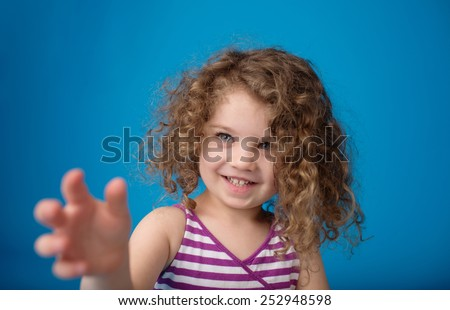 Happy smiling laughing child: girl with curly hair pointing at or reaching for something - stock photo