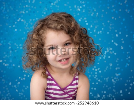 Happy smiling laughing child looking at camera: girl with curly hair against blue background with frozen snow flakes - stock photo