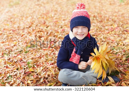 happy smiling little boy holding autumn leaves bouquet and enjoying fall weather in the park